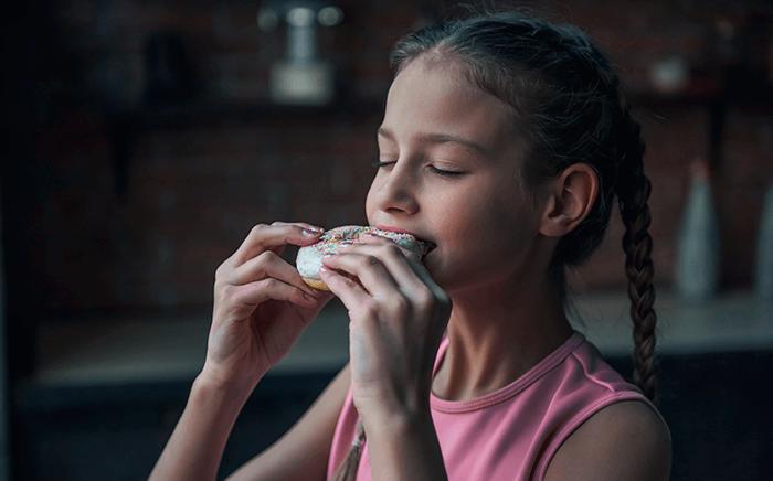 Niña comiendo donuts adornado con virutas de colores