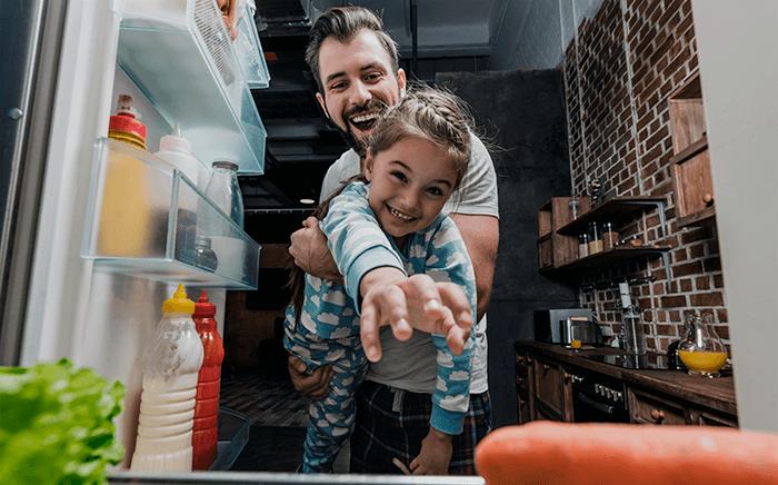 Adulto con niña jugando con el frigorífico abierto