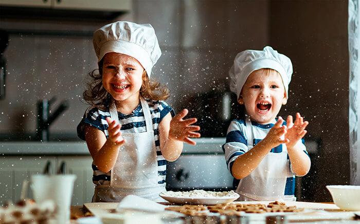 Niños con delantal de cocina jugando con harina en la cocina