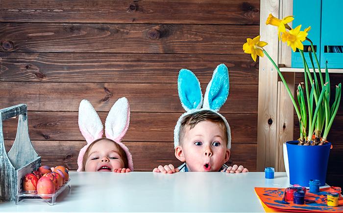 Dos niños disfrazados de conejo pintando huevos de pascua