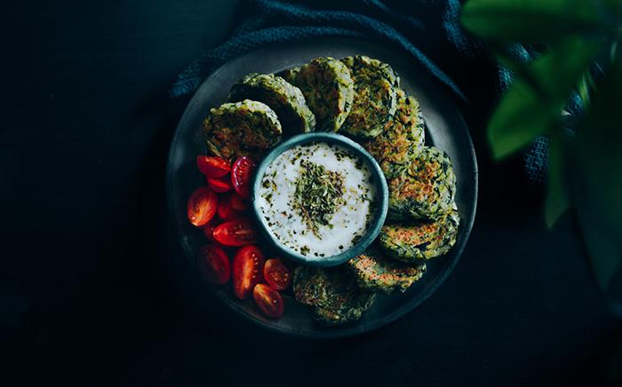 fritters de calabacin en plato con tomate