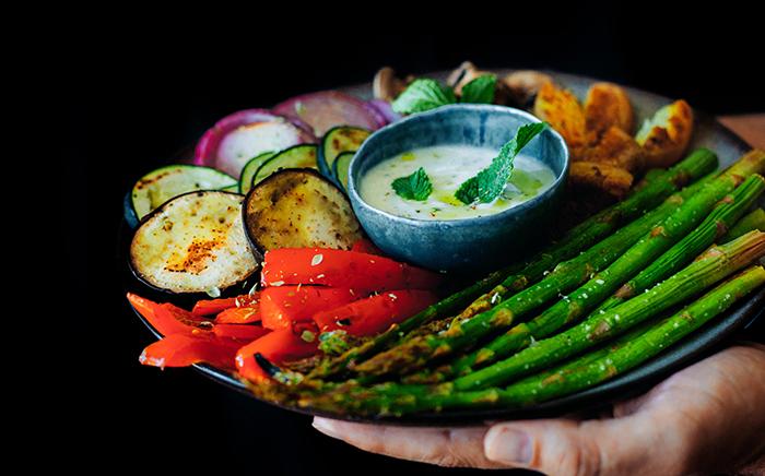 plato de verduras asadas con cuenco de salsa