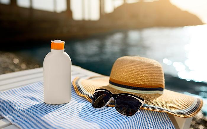 sombrero gafas de sol y crema solar en una toalla