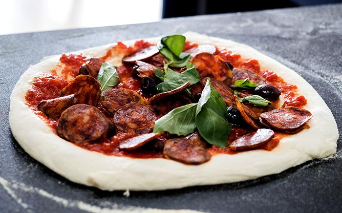 pizza sin hacer con chorizo y albahaca