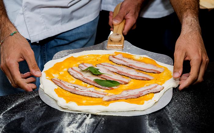 hombres sujetando pala de pizza con pizza de calabaza y panceta