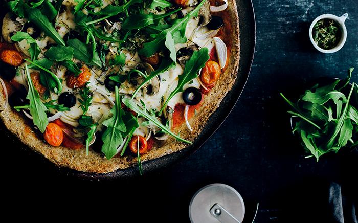 pizza con ingredientes vegetales en un plato con cortador de pizza y albahaca