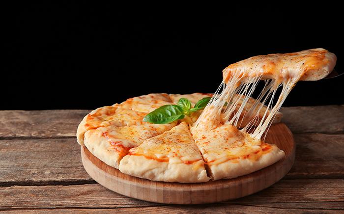 pizza con porción de pizza partida y elevada con queso derretido