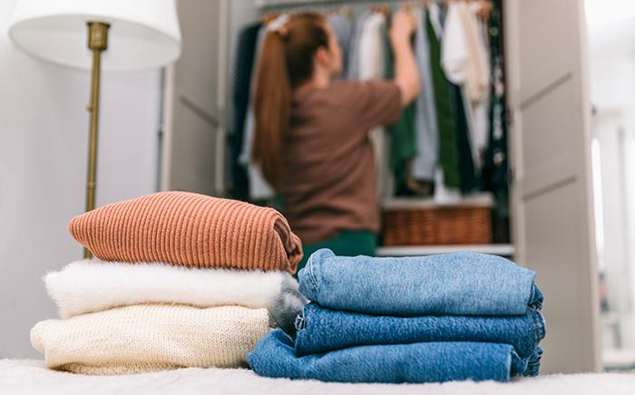 Ropa doblada en una cama con chica al fondo colocando ropa en un armario