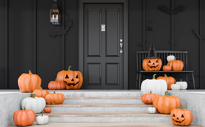 puerta negra de casa decorada con calabazas de halloween