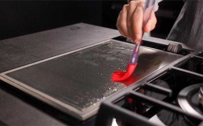 brocha de silicona expandiendo aceite sobre una placa de teppanyaki
