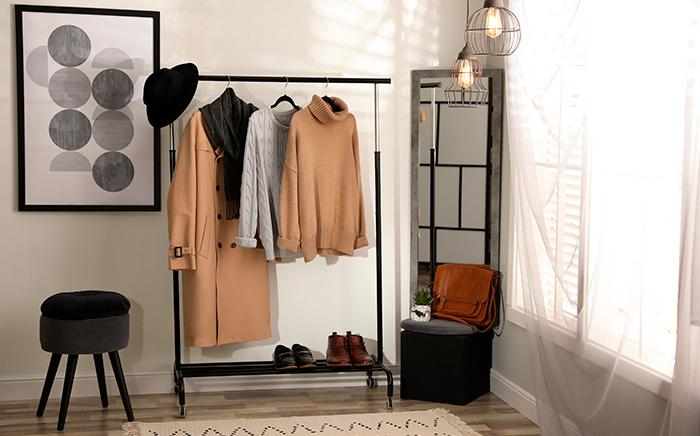 burro de ropa en habitación con un cuadro un taburete y ventana con cortinas